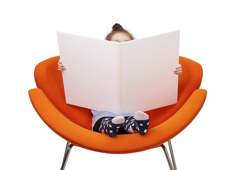 little kid reading big book in chair. Imagens