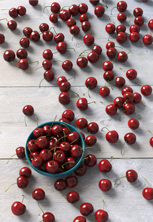red cherry in bowl on wooden table. 3d illustration