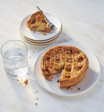 apple pie with a small piece on plate. Imagens