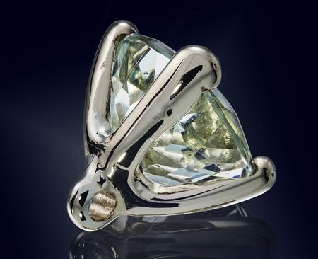 prasioliet quartz gem stone in golden setting isolated.