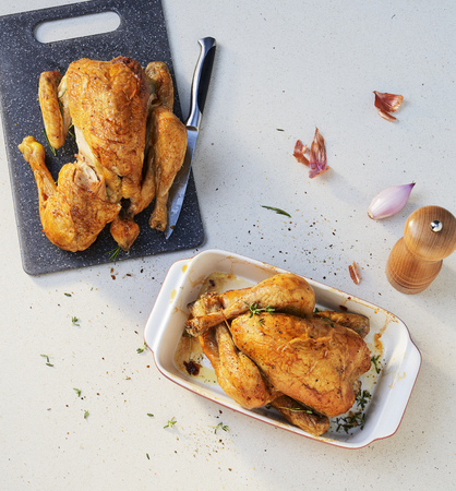 two hole chicken roasted on a cutting board. Imagens