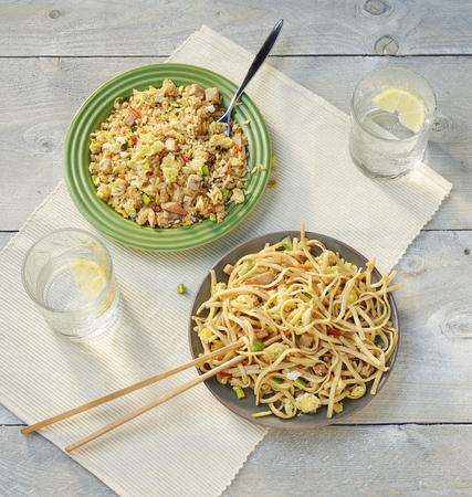 two dishes with chinese food on wooden table.