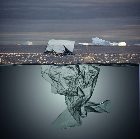 iceberg of garbage plastic floating in ocean with greenland background Imagens