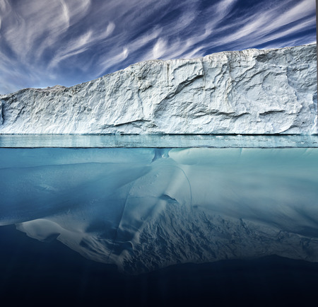 glacier with above and underwater view taken in greenland Imagens