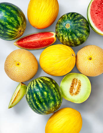 Watermelons, cantaloupes and sweet honeydew melon in a studio setting, isolated on white.
