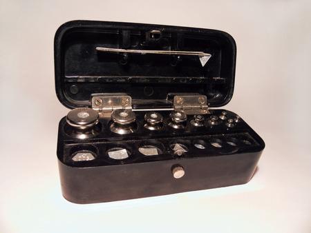 balanza de laboratorio: un conjunto de pinzas de laboratorio pesos de acero, doblado en una caja