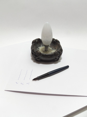 enumeration: frosted incandescent lamp in candlestick, dismantled fountain pen on the stack of paper with  inscriptions