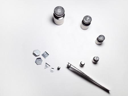 balanza de laboratorio: un conjunto de pesos de laboratorio y pinzas de acero Foto de archivo
