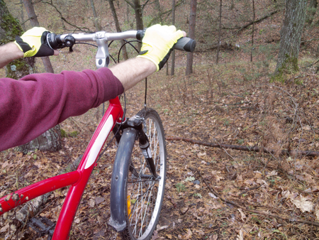 mans hands in bright cycling gloves, tightly holding the straight handlebar of the bicycle