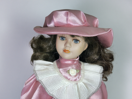 Porcelain doll with a delicate baby face, expressive features, clothing in retro style