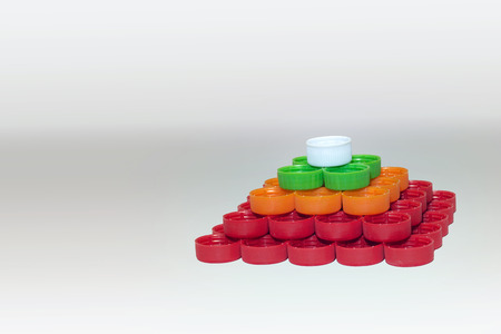 pyramid of whites, reds, greens, oranges striped caps of plastic bottles