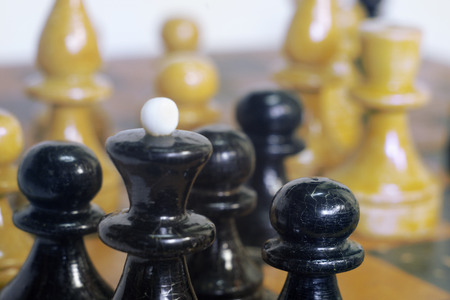 chess black king, surrounded by his pawns on the background of other chess pieces Stock Photo