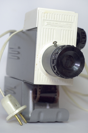 Vintage slide projector loaded with film. Front view on lens. Closeup