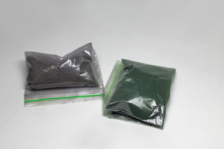 powder colorant for fabric. Two re-sealable plastic packs, closed on grip lock, with dark colors inside; with clipping path