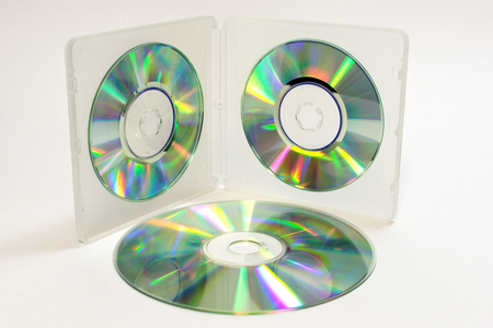 case for mini CDs; inner trays of double-sided semitransparent plastic box with iridescent discs on clips and normal sized disc is lying beside