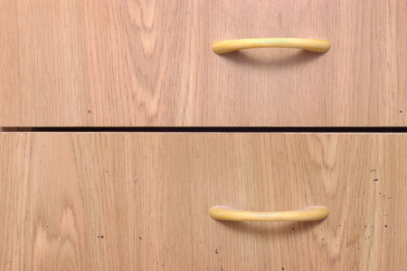drawer pull handle. bow-type, plastic, made in form of arcs, imitation of wood texture. front surface of furniture is stained with black spots Stock fotó