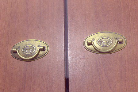 pair of brass folding pull handles on wooden doors of wardrobe Stock fotó