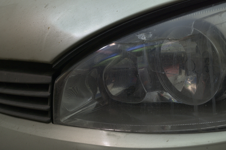 front left headlight of car with crack at the top of protective removable glass. lamp low and high beam and parking lights are switched off Stockfoto