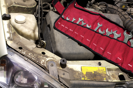 set wrenches in organizer unfolded under the hood of the car to service the engine. Arranged in the pockets under according numbers, in red fabric bag