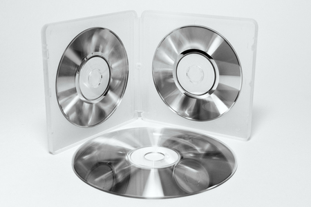 case for mini CDs. inner trays of double-sided semitransparent plastic box with iridescent discs on clips and stack of different sizes discs. black and white