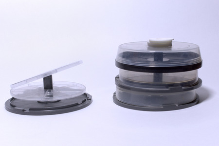 empty plastic storages for discs. tubes with transparent covers and cake box with two hard lids on spindle