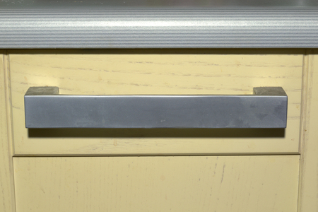 kitchen drawer knob under striped worktop. flat arch large handle with sharp corners. Silver tone, metal Stock fotó