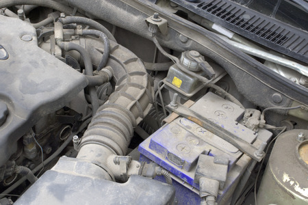 under the hood. duct hose transfer of air intake system, lead-acid car battery in clamping lock, brake fluid reservoir, fragment of engine. serviced components vehicle
