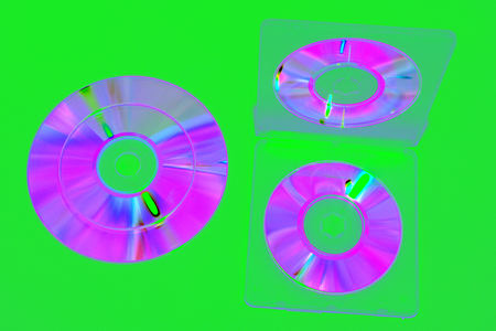 image in complementary colors tones : double-sided plastic box for mini CDs, open. iridescent compact discs on green background.