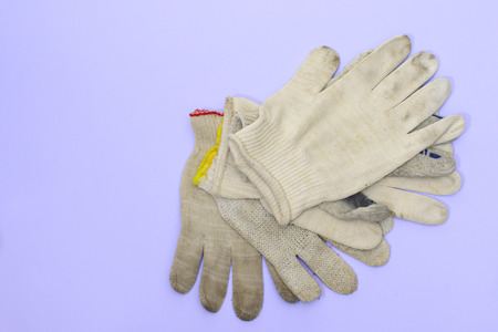 a small stack of simple cloth gloves for manual labor on a purple-blue background Stock Photo