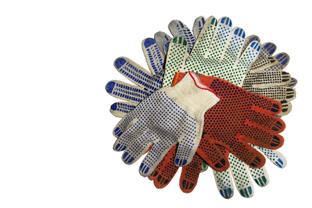 big stack of knitted protective gloves with colored dots on working sides and stretchable cuffs, isolated on white background, with clipping path