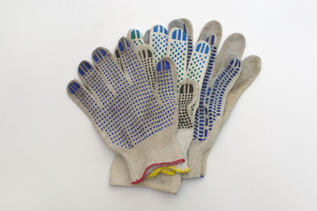 stack of cotton gloves with multicolored rubber dots, elastic cuffs, bordered by blue, red and yellow hems. Working protective wear, knitted, of natural yarn strings