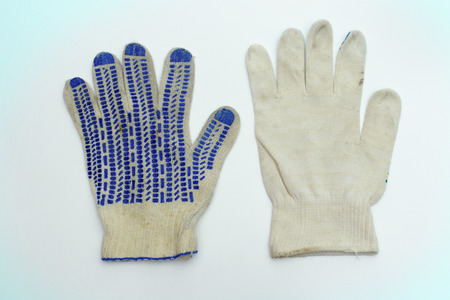 protective gloves of white fabric. intended for manual labor. pair with blue rubber dots on working side and stretchable cuff with thin strip on hem. one of them lies face down. blue hue of background