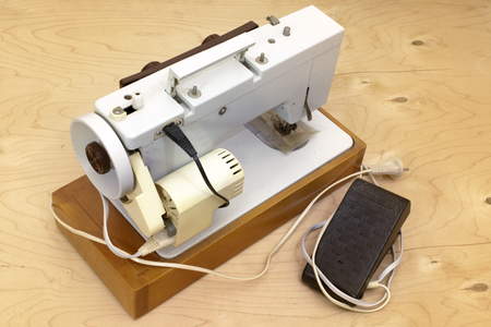 desktop professional electric sewing machine. electric motor on the rear side, belt drive, hidden in protective housing, equipped with a foot pedal controller. on wooden platform Stock fotó