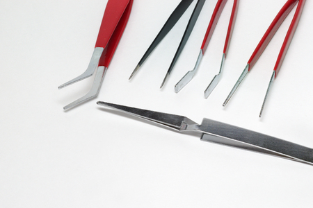 steel tweezers for precision electronics repairing. Different types of tools: pointed tip, curved forceps and clamp on foreground