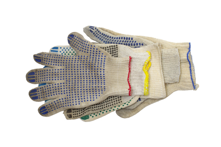 stack of knitted working gloves with colorful rubber dots, neatly arranged on the white background. elastic cuffs, bordered by blue, red and yellow hems. Isolated, with clipping path Stock fotó