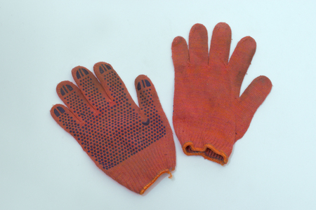 work gloves of orange-red cotton. one is turned inside out. pair with stretchable cuff with bright orange hem. clipping path