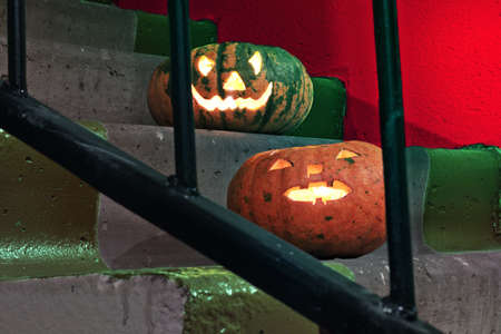 two jack-o'-lantern. Nice pumpkins on the stairs behind the bars of the railings Imagens