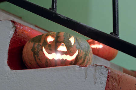 cheerful and evil face carved from pumpkin for Halloween holiday. Pumpkin head smiles at the stair step