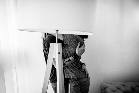 Loving couple kissing and hugging behind a large lamp near the window in a light room. Black-and-white photo, side view