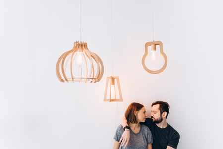 Cute spouses hug each other. Love story. White background, three lamps, side view