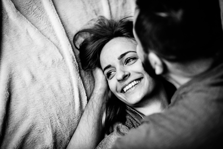 Husband kisses his beloved wife in the bedroom on the bed. Love story, black and white photo, top view
