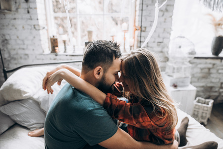 Wife hugging her husband. They spend time together at home. Love story, side view Stock Photo
