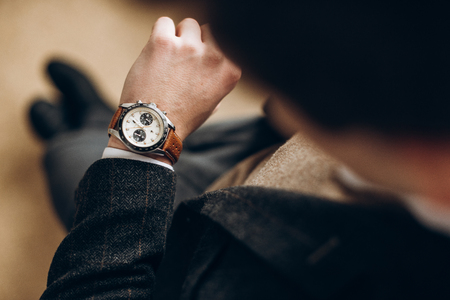 Businessman is checking time on his modern wrist watch. Top view Banque d'images