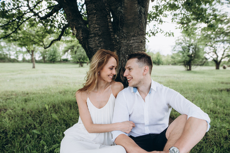 A beautiful couple is resting outside the city, sitting near a big tree in the garden and smiling. Love story Stock Photo