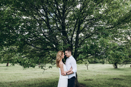 Handsome guy and an attractive girl hug each other near a large green tree in the garden. Love story