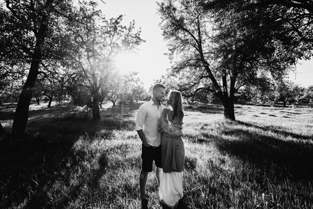A loving couple walks through the garden among the beautiful fruit trees at sunset. Black and white photo Stock Photo
