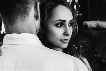 Black and white photo on which the guy hugs his beloved beautiful girl Stock Photo