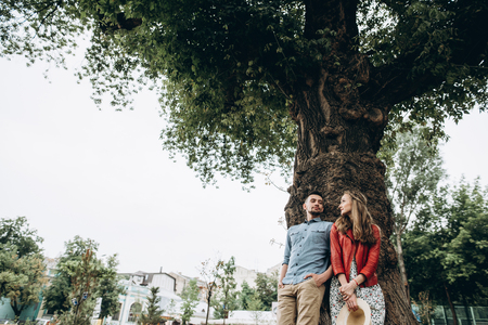 A stylish young couple stands near a big tree and lovingly look at each other. Love story