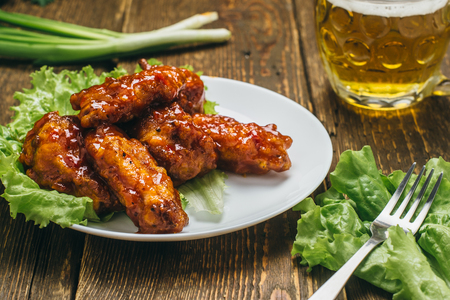 Chicken wings with lettuce, leek and beer on a wooden table