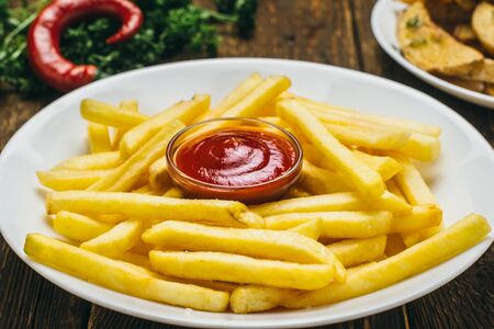 Crispy french fries on a white round plate with tomato sauce and parsley